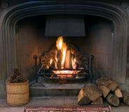 Chimenea de piedra con un fuego encendido del rugido Imágenes de archivo libres de regalías