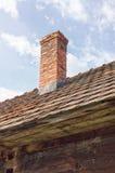 Chimenea del ladrillo en el tejado de teja de una casa de madera vieja fotos de archivo