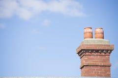 Chimenea del ladrillo rojo en el tejado con el cielo azul Foto de archivo
