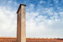 Chimenea en el tejado de teja roja con el fondo del cielo nublado Fotos de archivo libres de regalías