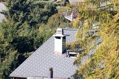 Chimenea en el top de las tejas de tejado de madera de la roca del chalet de la casa imagenes de archivo