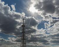 Chimenea que fuma de la refinería de petróleo contra el cielo nublado y el sol Fotos de archivo libres de regalías