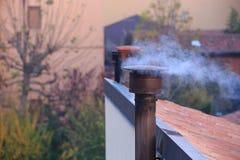 Chimenea que fuma de una casa Foto de archivo libre de regalías