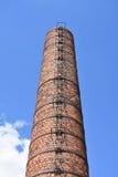 Chimenea vieja de la fábrica del ladrillo rojo con el ledder Fotografía de archivo libre de regalías