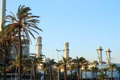 Chimeneas de la central eléctrica del ciclo combinado del ² s de Besà detrás de palmtrees imagen de archivo libre de regalías