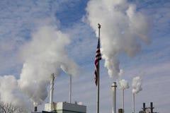Chimeneas de la fábrica y bandera americana Foto de archivo libre de regalías