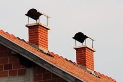 Chimeneas del ladrillo rojo con la protección del metal en el top en casa suburbana inacabada de la familia en la puesta del sol imagen de archivo libre de regalías