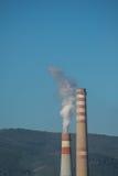 Chimeneas industriales con el humo blanco en el cielo azul Fotos de archivo libres de regalías