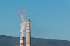 Chimeneas industriales con el humo blanco en el cielo azul Imágenes de archivo libres de regalías