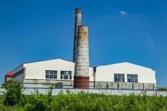 Chimeneas industriales contra el cielo azul imagen de archivo