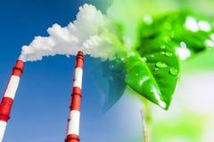 Chimeneas industriales de la fábrica en el fondo de plantas verdes imágenes de archivo libres de regalías