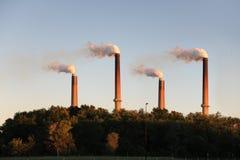Chimeneas industriales en la puesta del sol Imagenes de archivo