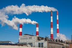 Chimeneas que fuman contra el cielo azul Imagen de archivo