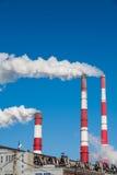 Chimeneas que fuman contra el cielo azul Foto de archivo libre de regalías