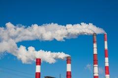 Chimeneas que fuman contra el cielo azul Fotos de archivo libres de regalías