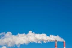 Chimeneas que fuman contra el cielo azul Foto de archivo