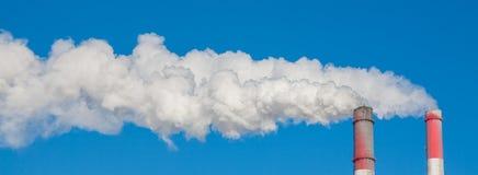 Chimeneas que fuman contra el cielo azul Fotografía de archivo libre de regalías