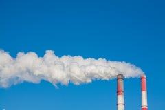Chimeneas que fuman contra el cielo azul Fotos de archivo