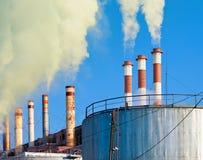 Chimeneas que fuman industriales contra el cielo Imagen de archivo libre de regalías
