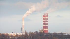 Chimeneas que fuman la fábrica contra el cielo Fotos de archivo