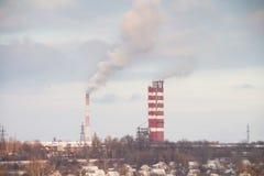 Chimeneas que fuman la fábrica contra el cielo Imágenes de archivo libres de regalías