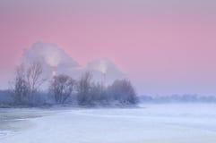 Chimeneas que fuman sobre un río brumoso y de congelación durante oscuridad imagen de archivo