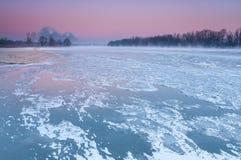 Chimeneas que fuman sobre un río brumoso y de congelación durante oscuridad imagen de archivo libre de regalías