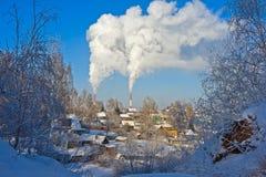 Chimeneas y casas de la aldea que fuman en invierno Imágenes de archivo libres de regalías