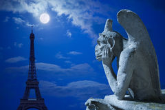 Chimera and Eiffel tower under moonlight royalty free stock photos