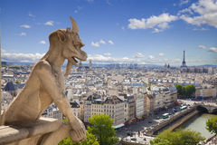 Chimera from Notre Dame of Paris. Demon overlooking the Eiffel Tower at a summer day Stock Photos