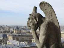Chimera of pensive demon. Le Stryge - best known chimera from seated on gallery of Notre Dame Cathedral, Paris, France Stock Photography