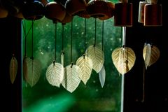 Chimes hanging in the window, Decorative bells hang on the window behind with bokeh background. The traditional wind bell fluttering in tropical wind in Thai stock photo