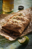 Chimichanga with lime, cream, chilly and beer. On a vintage board royalty free stock photography