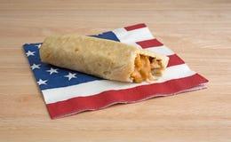 Chimichanga mordido del pollo y del queso en servilleta Imagen de archivo libre de regalías