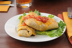 Chimichangas topped with cheddar cheese Stock Images