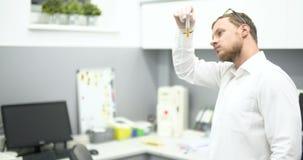 Chimico Adding Chemicals in un esperimento della boccetta di miscelazione video d archivio