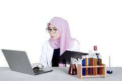 Chimico asiatico con il computer portatile e la provetta Immagini Stock
