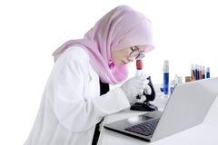 Chimico femminile con il microscopio Fotografia Stock