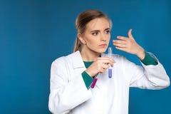 Chimico femminile con una provetta su un fondo blu Fotografia Stock Libera da Diritti
