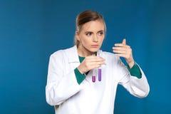 Chimico femminile con una provetta su un fondo blu Fotografia Stock