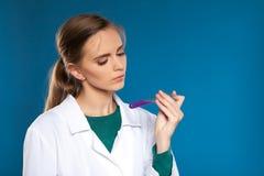 Chimico femminile con una provetta su un fondo blu Fotografie Stock Libere da Diritti