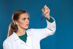 Chimico femminile con una provetta su un fondo blu Immagine Stock