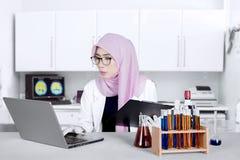 Chimico musulmano con il computer portatile e la lavagna per appunti Fotografia Stock Libera da Diritti