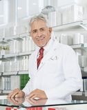 Chimico sicuro Smiling At Counter in farmacia fotografia stock
