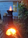 Chiminea fire burning in a backyard. Flames from a fiercely burning fire in a chiminea in a back garden Royalty Free Stock Photo