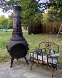 Chiminea Fire Pit with Texas Star wood holder. A Chiminea Fire Pit with Texas Star wood holder surrounded by trees and a wooden fence stock image