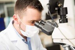 Chimiste masculin épuisant le microscope étroit photographie stock
