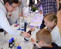 Chimistes tak de laboratoire par jour hors du laboratoire pour enseigner des enfants au sujet de chimie en tant qu'élément de la  photo libre de droits