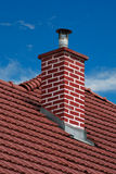 Chimney. Closeup of red roof covering with brick-made chimney Royalty Free Stock Image