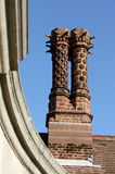 Chimney. Detail of an old decorated chimney against blue sky Royalty Free Stock Images